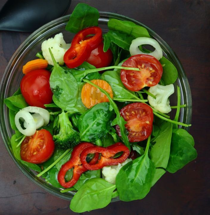 36630921 - bowl of fresh colorful salad with fork and spoon on wooden surface